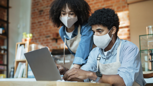 Photo of two small business owners wearing face masks while working at a laptop