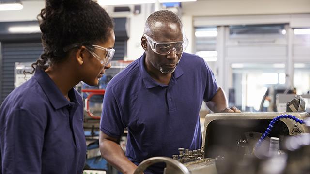 Black engineer with teenage apprentice
