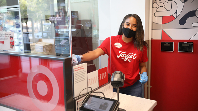 Photo: A smiling Target team member wearing a red Target shirt, black face mask and blue gloves, standing behind a Plexiglass shield at the Order Pickup counter