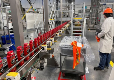 A person works with robots at Procter & Gamble's Tabler Station factory in Martinsburg, W.Va., on May 28. (Timothy Aeppel/Reuters)