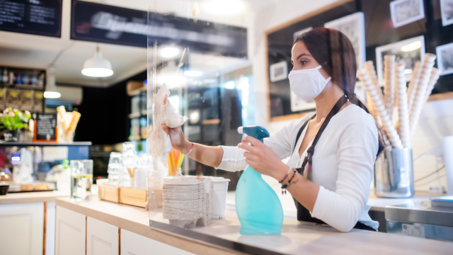 Photo of a young woman with a face mask working in a cafe, wiping down a plastic barrier.