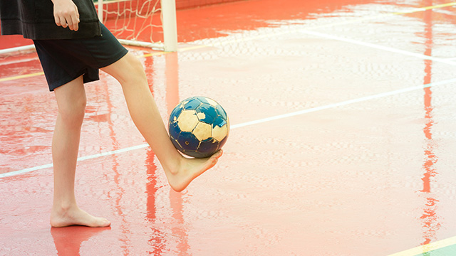 Barefoot boy playing football on a wet sports court