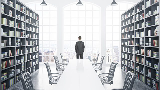 Business person looks out window of board room library
