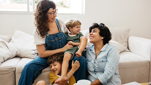 Queer couple playing with their children at home.